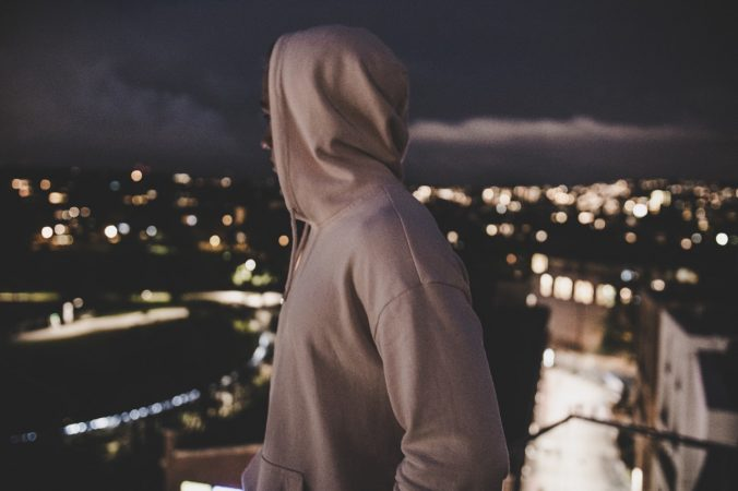 Man in Hoodie Overlooking City